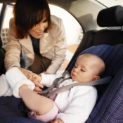 Mother placing baby in child seat